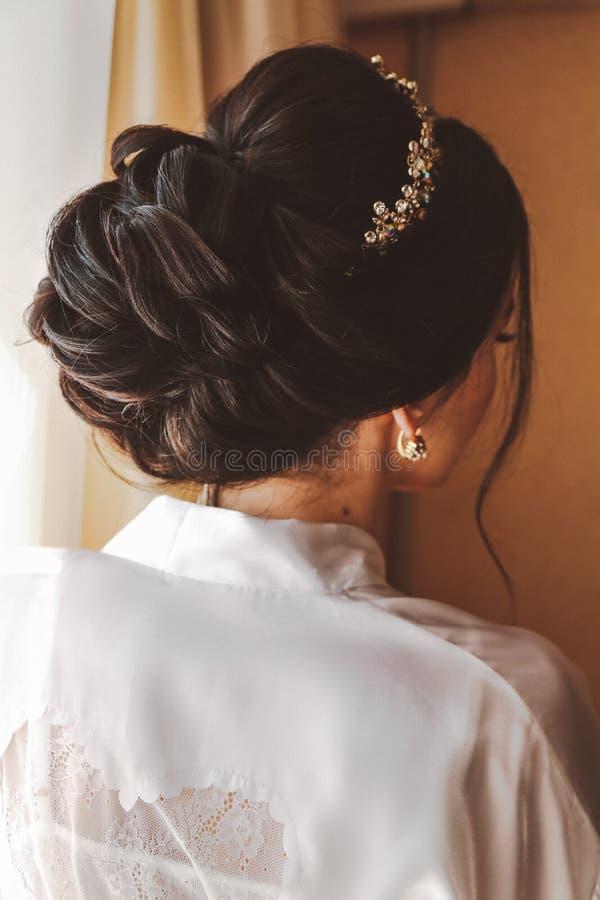 Beautiful bride with dark hair preparing herself in her wedding stock image