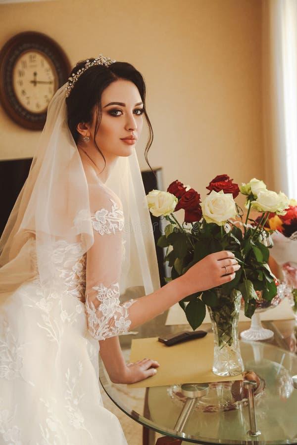 Beautiful bride in elegant wedding dress and diadem posing in r royalty free stock photo