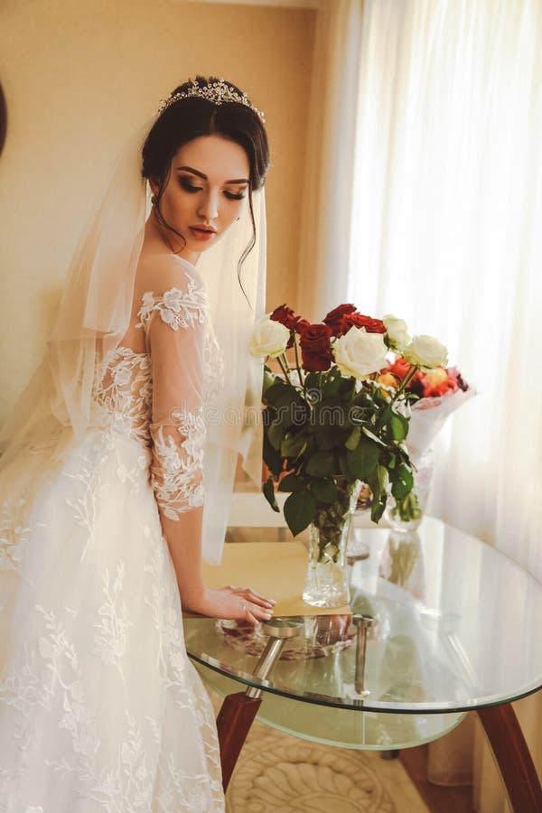 Beautiful bride in elegant wedding dress and diadem posing in r royalty free stock images