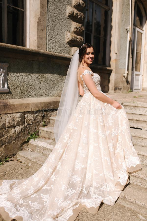 Beautiful bride in elegant wedding gress go up the stairs. Big train drees.  royalty free stock image