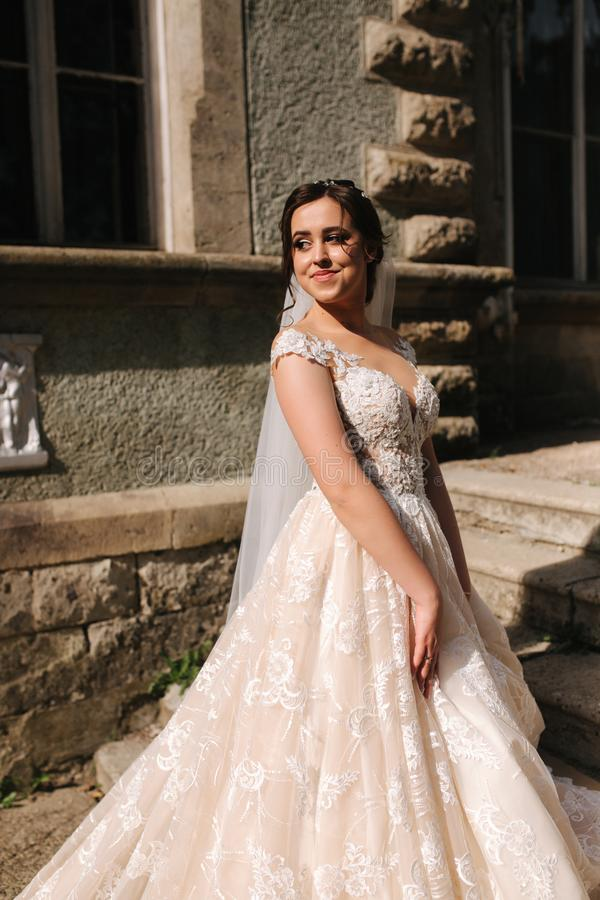 Beautiful bride in elegant wedding gress go up the stairs. Big train drees.  royalty free stock photography