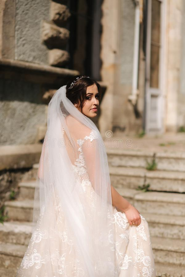 Beautiful bride in elegant wedding gress go up the stairs. Big train drees.  stock image