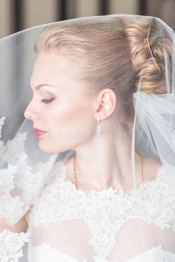 Beautiful bride with fashion wedding hairstyle. Closeup portrait of young gorgeous bride. royalty free stock photography