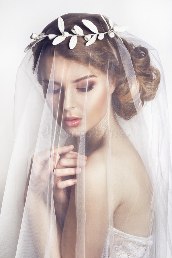 Beautiful bride with fashion wedding hairstyle - on white background. Closeup portrait of young gorgeous bride. Wedding. Studio shot.Beautiful bride portrait stock photo