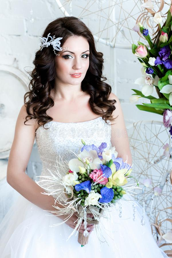 Beautiful bride with flowers looking at us happily stock images