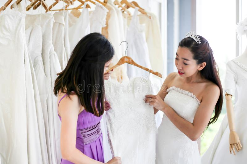 Beautiful bride getting dressed by her best friend in her wedding day and choosing a wedding dress in the shop and the shop stock photos