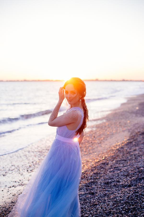 Bride in blue dress. Beautiful bride girl in a blue dress with long hair at sunset stock photo
