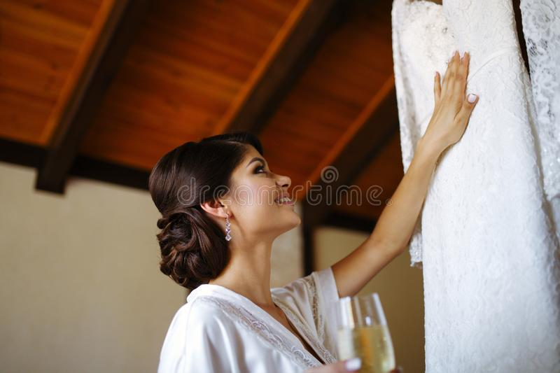 Beautiful bride girl with a glass of champagne in hand near a wedding dress stock images