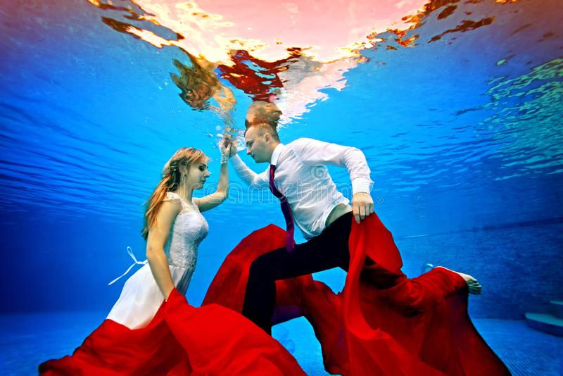 The beautiful bride and groom dance underwater with each other and pose with a red cloth in their hands on a blue background on a royalty free stock image