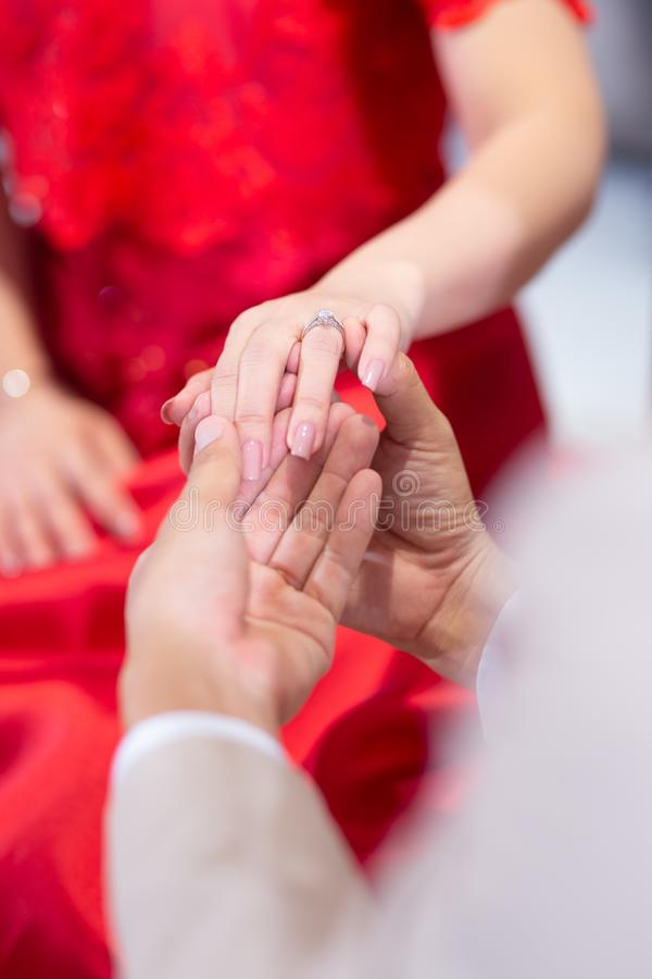 Beautiful bride and groom hands exchanging wedding rings in chur royalty free stock images