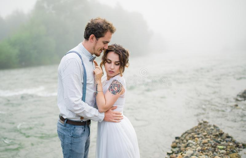 Wedding couple, groom and bride near wedding arch on a background mountain river royalty free stock photography