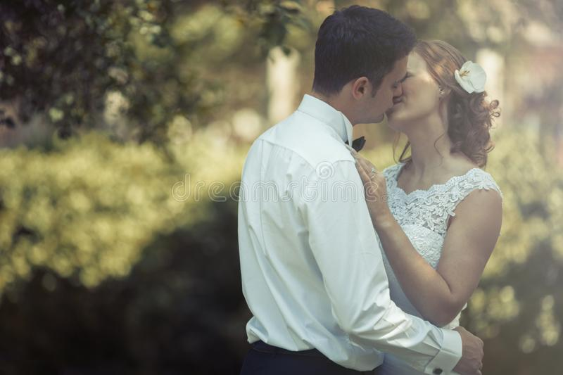 Beautiful bride and groom kissing outdoors stock photos