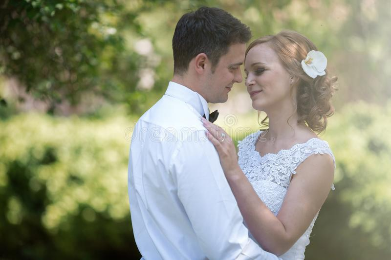 Beautiful bride and groom kissing outdoors stock photo