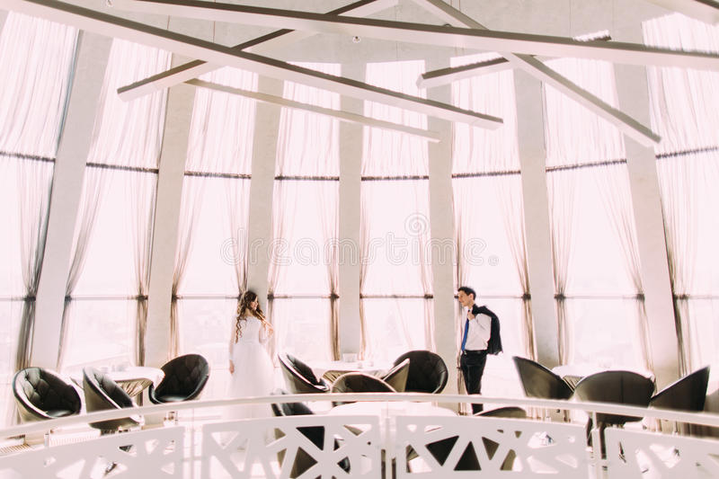 Beautiful bride and groom in modern stylish interior of the restaurant stock image