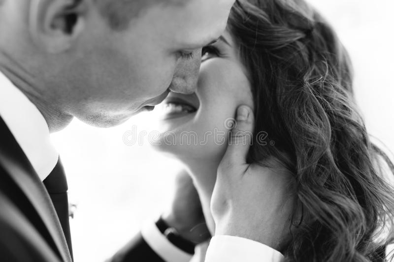 Beautiful bride and groom posing in Studio, first kiss wedding photo shoot royalty free stock photography