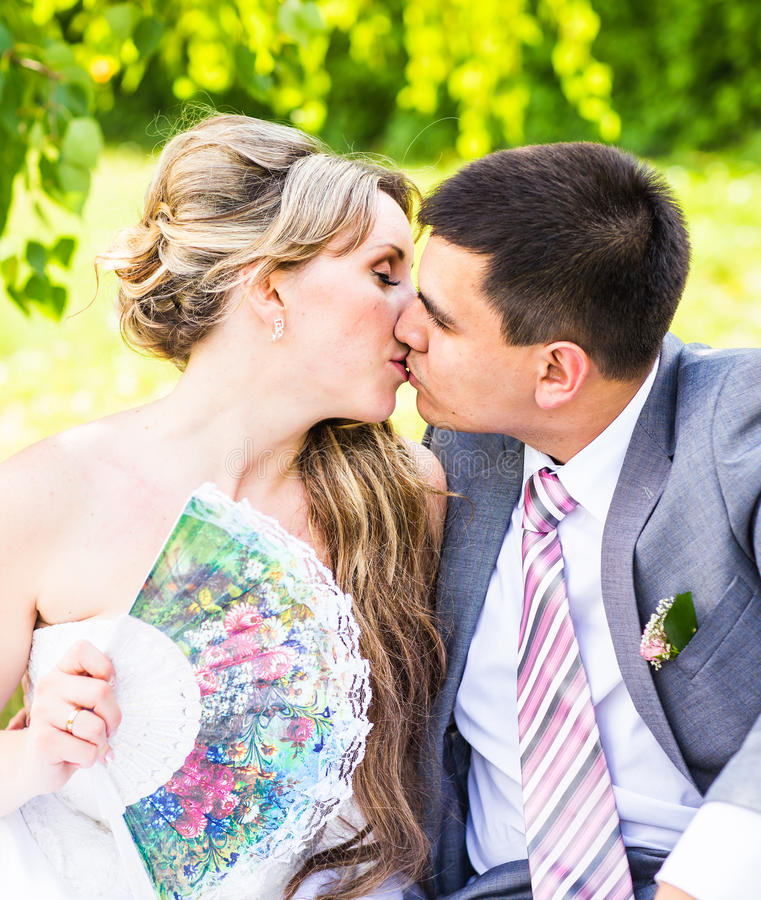 Beautiful bride and groom sitting in grass and kissing. Young wedding couple stock photos