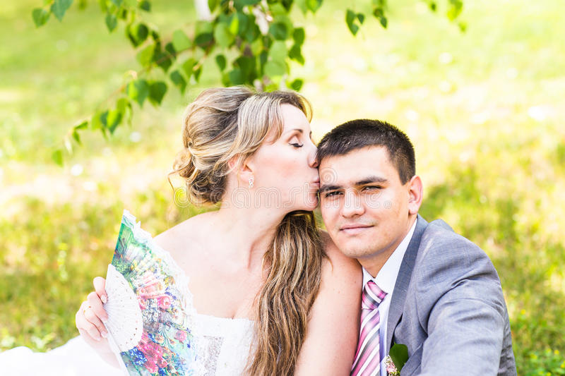 Beautiful bride and groom sitting in grass and kissing. Young wedding couple royalty free stock images