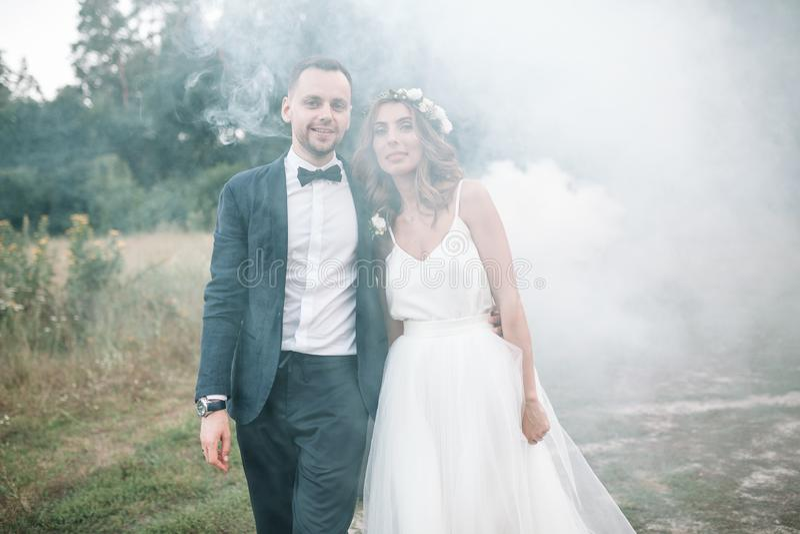 Beautiful bride and groom. Wedding ceremony in nature. Smoke bombs. stock photo