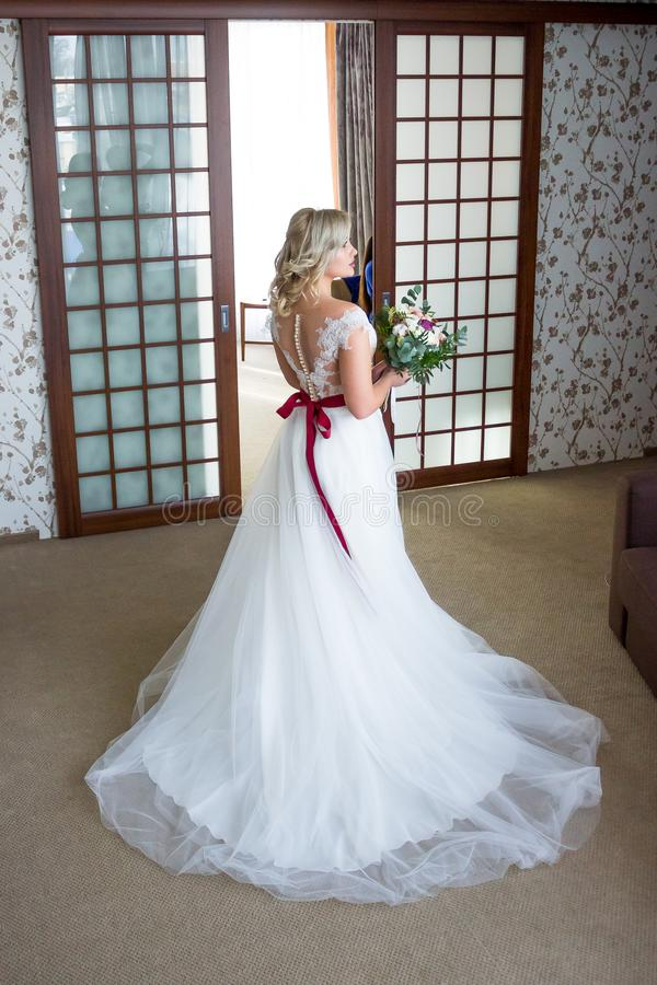 Beautiful bride with hair and makeup suits wedding dress with lacing at the back and a wedding bouquet in the background stock photo