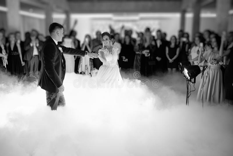 Beautiful bride and handsome groom dancing first dance at the wedding party. stock photography