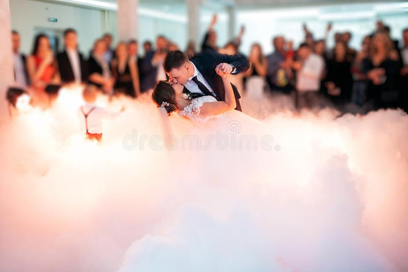 Beautiful bride and handsome groom dancing first dance at the wedding party. stock images