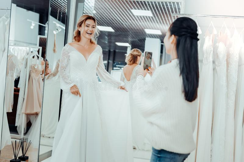 Beautiful bride and her bridesmaid taking pictures of a dress. stock photos