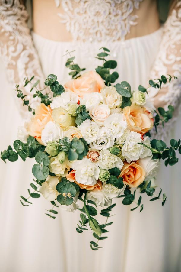 Beautiful bride is holding a wedding colorful bouquet. Beauty of colored flowers. Close-up bunch of florets. stock images