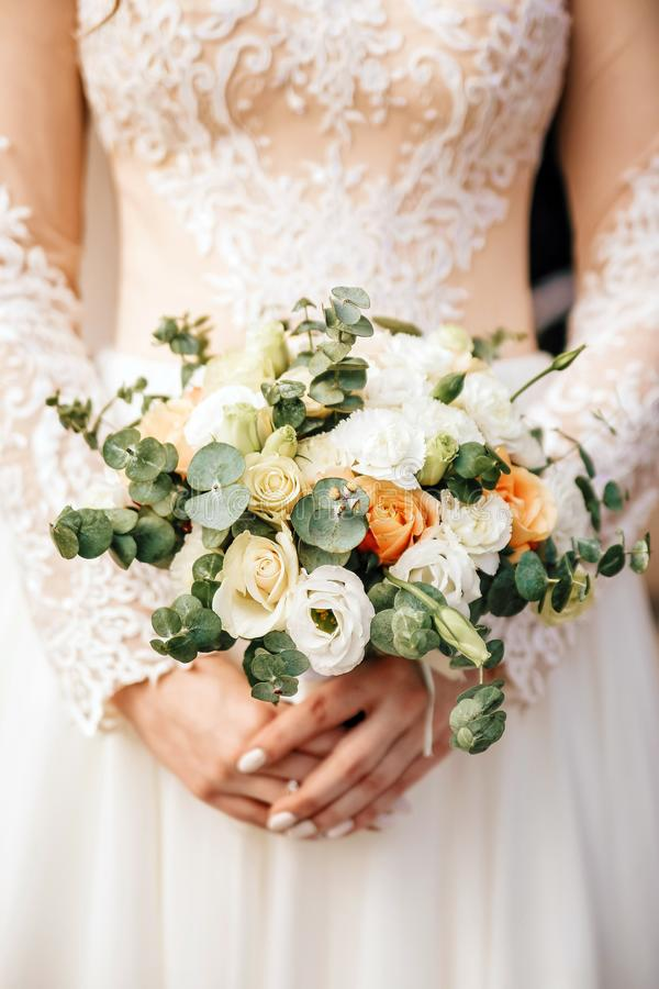 Beautiful bride is holding a wedding colorful bouquet. Beauty of colored flowers. Close-up bunch of florets. royalty free stock photo
