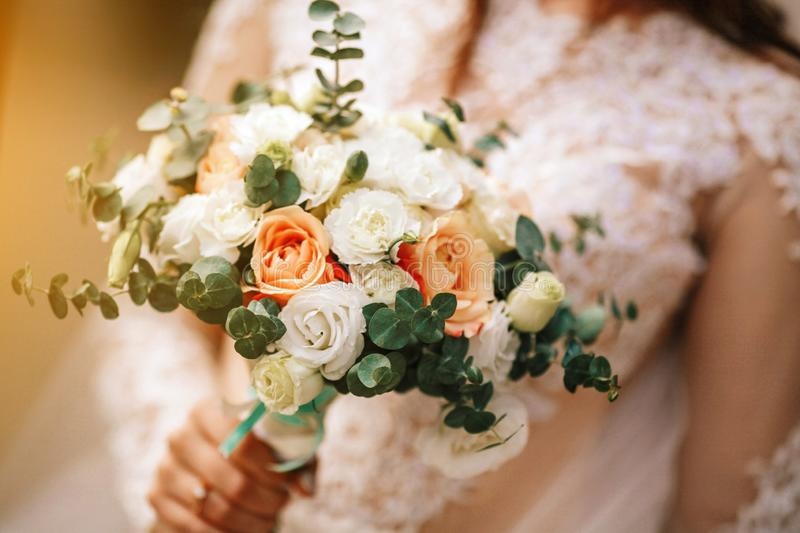 Beautiful bride is holding a wedding colorful bouquet. Beauty of colored flowers. Close-up bunch of florets. royalty free stock photography