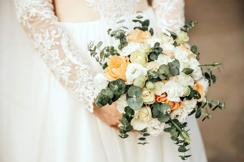 Beautiful bride is holding a wedding colorful bouquet. Beauty of colored flowers. Close-up bunch of florets. stock photography