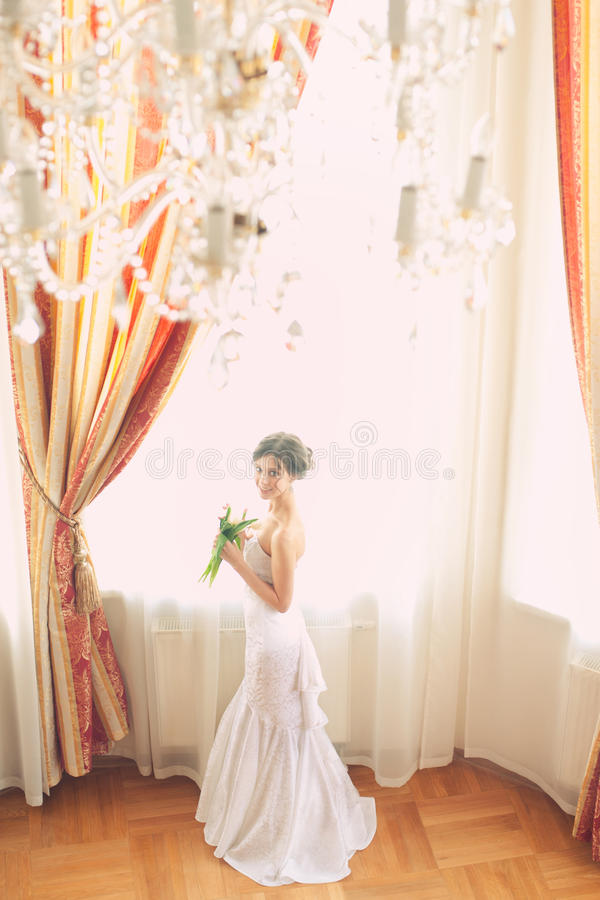 Beautiful bride indoors. Beautiful bride in white wedding dress standing near the window indoors stock photo
