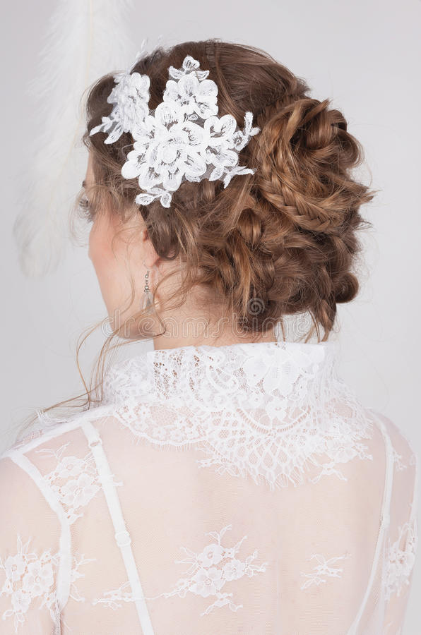 Beautiful bride with lace flowers in her gorgeous dark blond hair. High wedding hairstyle, braids and curls stock photos