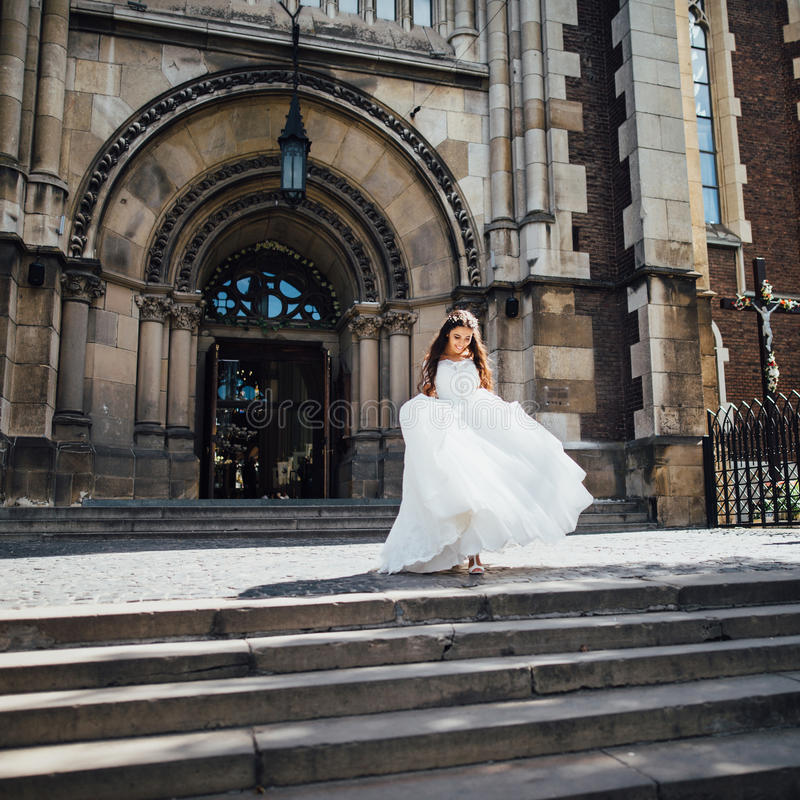 Beautiful bride leaves the church and goes upstairs. And smiling stock photos
