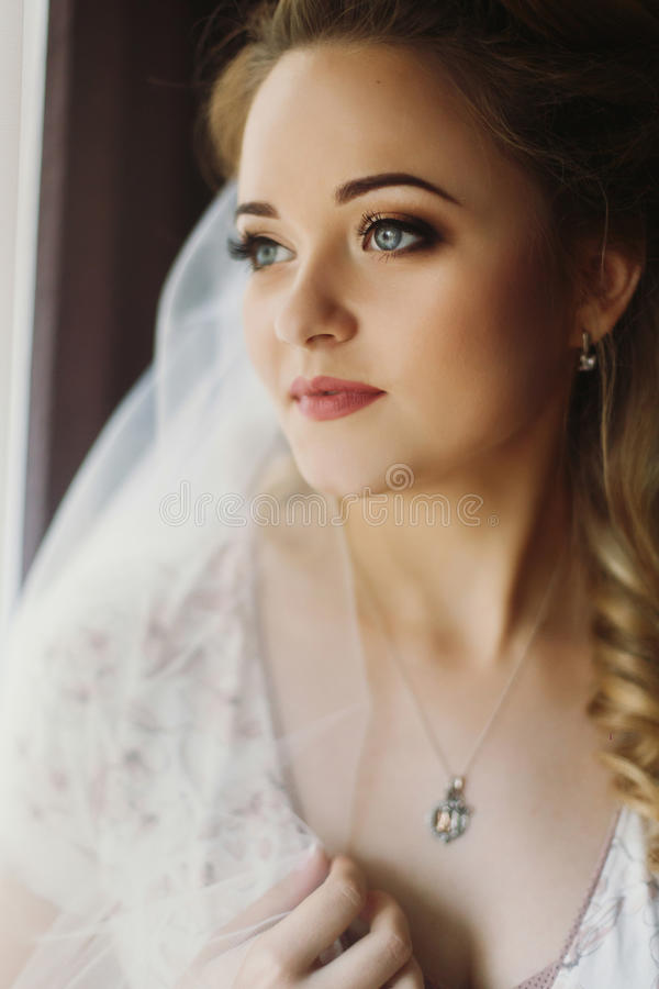 Beautiful bride looking out of window, morning wedding preparation, sensual blonde woman in robe and veil portrait in royalty free stock image