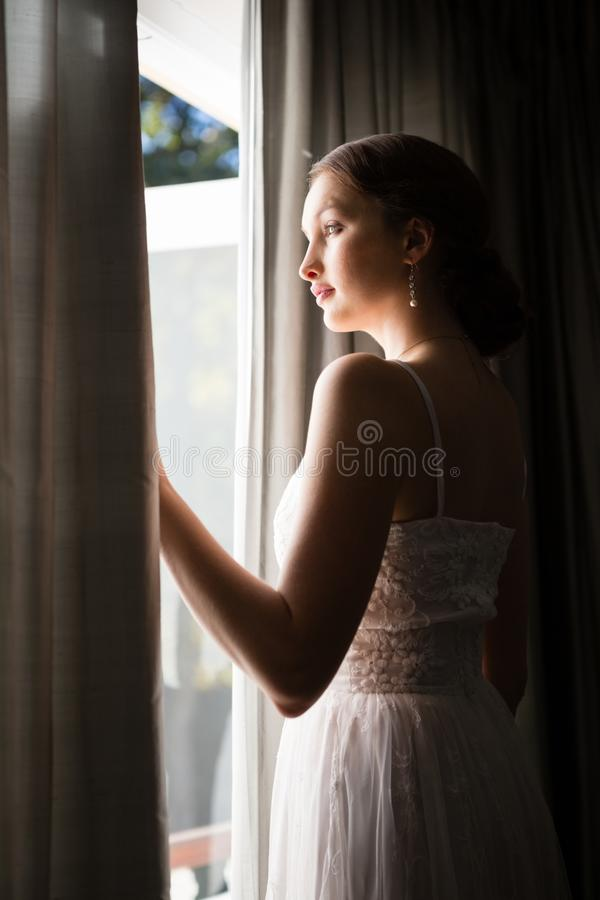 Free Beautiful Bride Looking Through Window While Standing In Darkroom At Home Stock Image - 99962821