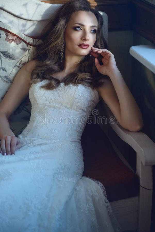 Beautiful bride in luxurious wedding dress with sweetheart neckline sitting ion the vintage sofa in relaxed pose royalty free stock photo
