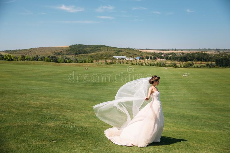 Beautiful bride in luxury fashion white wedding dress with veil on the green golf club glade, wedding day. Amazing full. Length body portrait of girl. Marriage stock photos