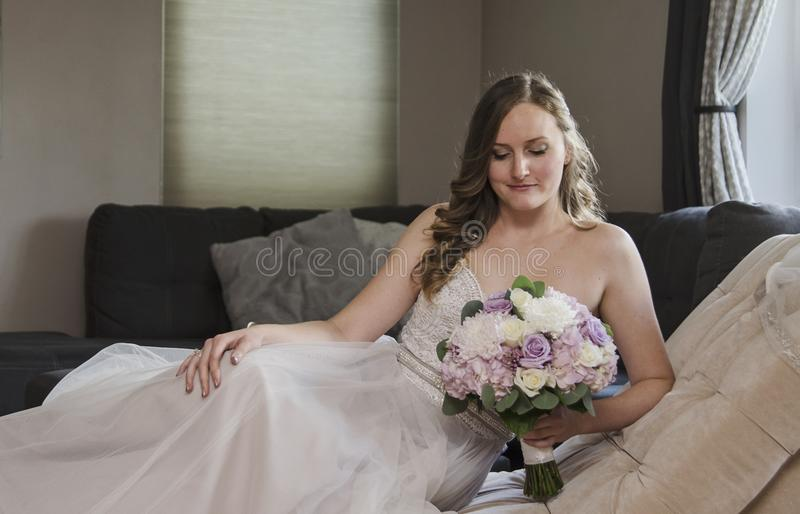 Beautiful bride lying on chaise lounge stock images