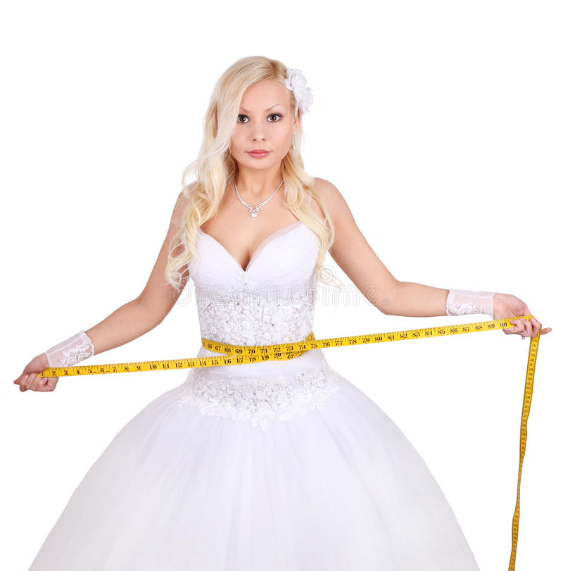 Beautiful bride with measuring tape. Bride measuring her wedding dress isolated on white stock image