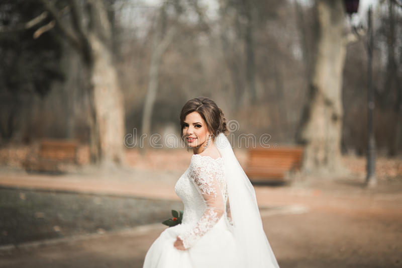Beautiful bride in the park on her wedding day with bouquet stock image