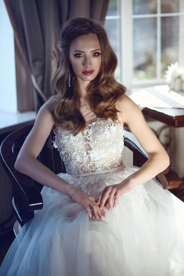 Beautiful bride in luxurious A-line wedding dress sitting in the vintage arm chair stock photos