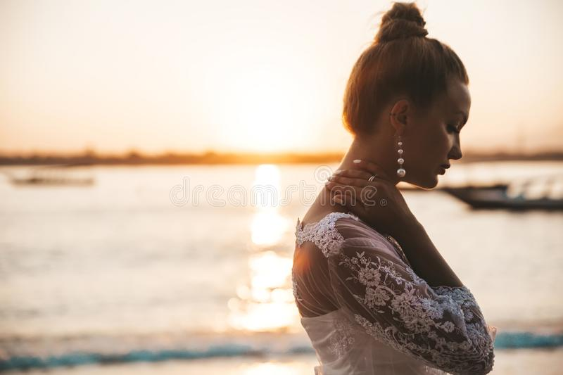 Beautiful bride posing on the beach behind sea at sunset royalty free stock image