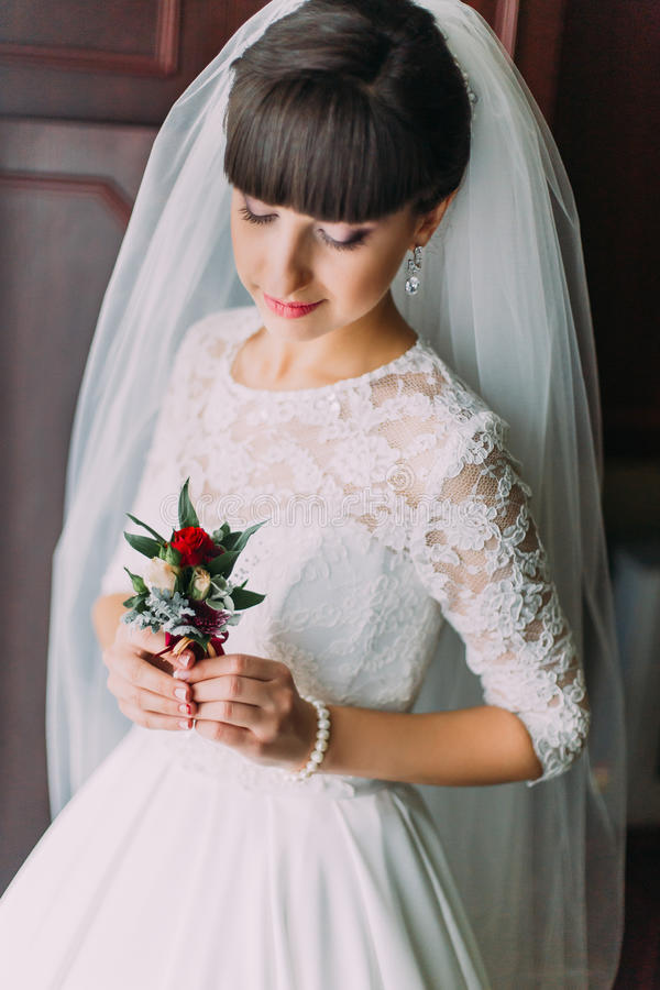 Beautiful bride posing with cute floral boutonniere indoors before her wedding royalty free stock photos