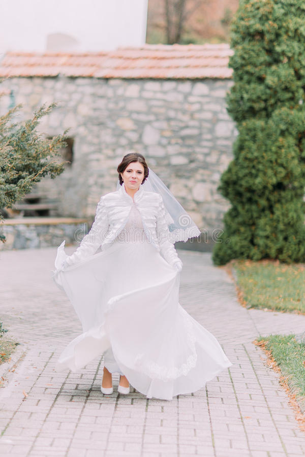 Beautiful bride posing in green sunny park waving her elegant wedding dress stock photo