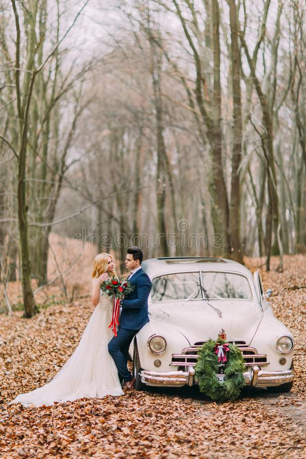 Beautiful wedding couple posing near the car in forest royalty free stock photography