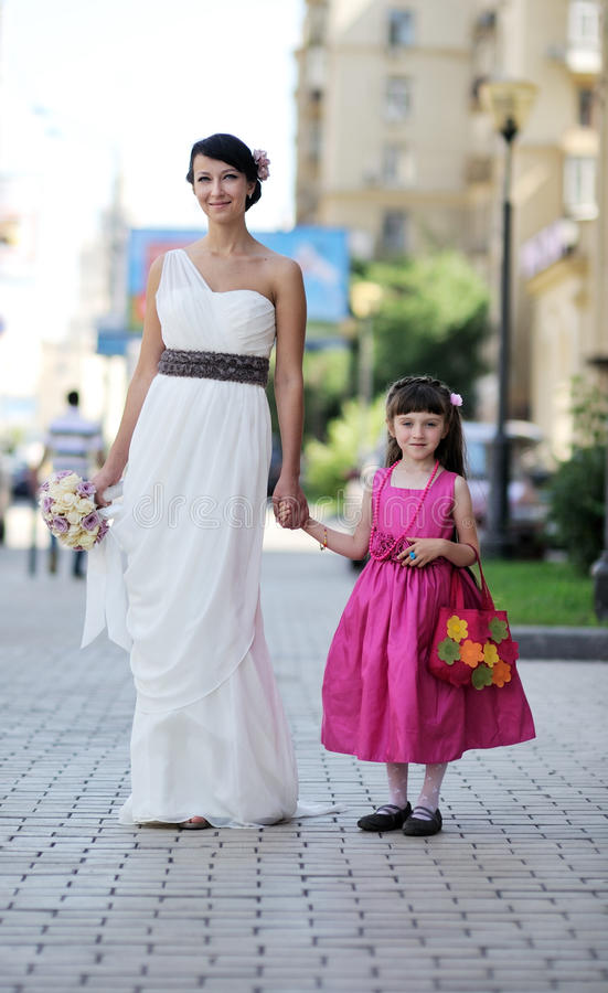 Beautiful bride posing together with flowergirl stock photo