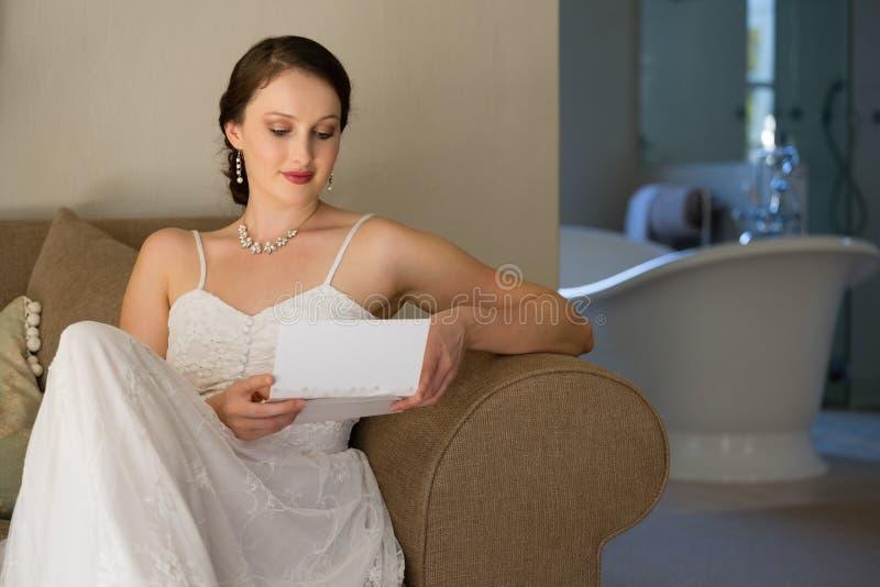 Beautiful bride reading wedding card while sitting on sofa royalty free stock image