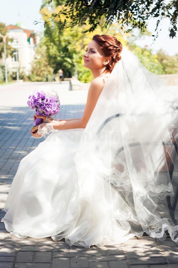 Beautiful bride with red hair in a white wedding dress and long veil sitting on a park bench, looking up. Holding a bouquet of lilac lisianthuses and white stock image