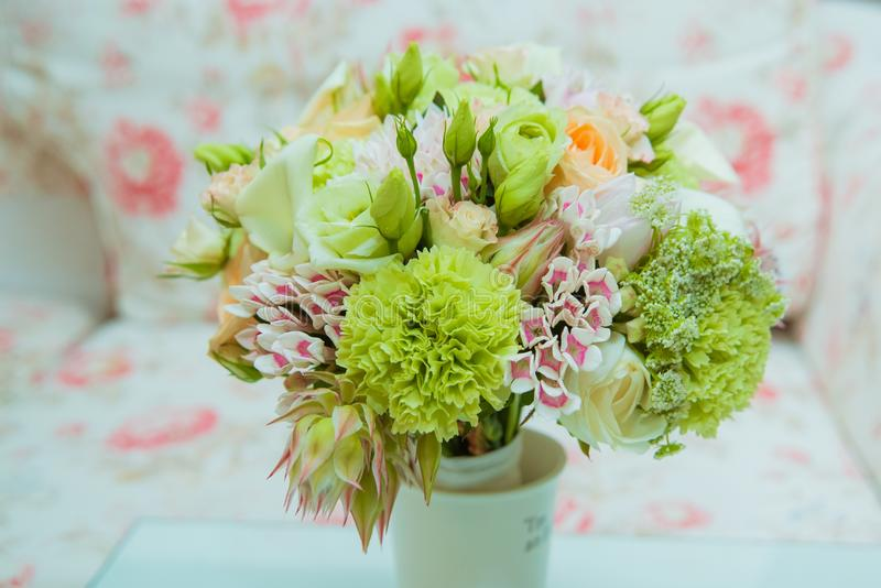 A beautiful bride`s bouquet of delicate shades of green, pink, orange and white flowers is in a vase on the wedding day royalty free stock image