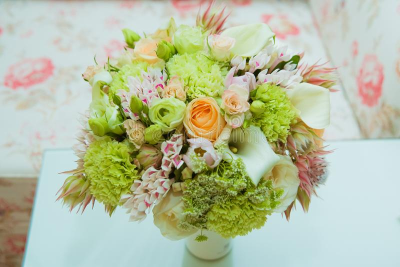 A beautiful bride`s bouquet of delicate shades of green, pink, orange and white flowers is in a vase on the wedding day royalty free stock photos
